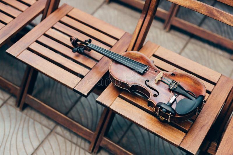 Foto del violín de madera en sillas Tiro horizontal Música en directo en la ocasión especial Foto al aire libre Instrumento music imagen de archivo libre de regalías