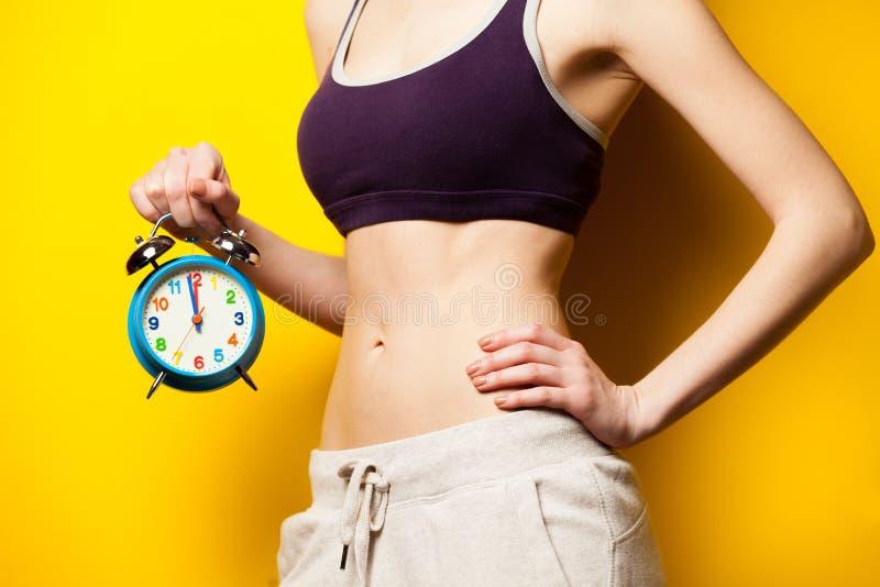 Foto dell'ente femminile esile perfetto con la sveglia nella mano o immagini stock libere da diritti