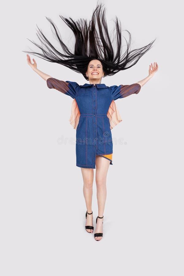 Foto dell'interno di giovane bella donna sorridente felice che gioca con i suoi capelli lunghi Vestito alla moda d'uso di modello immagini stock