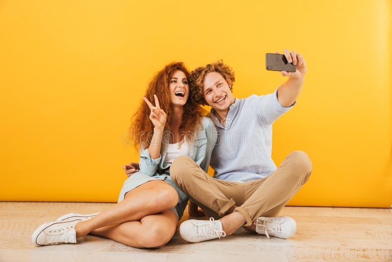 Foto dell'uomo bello delle coppie allegre e della seduta riccia della donna 20s immagine stock