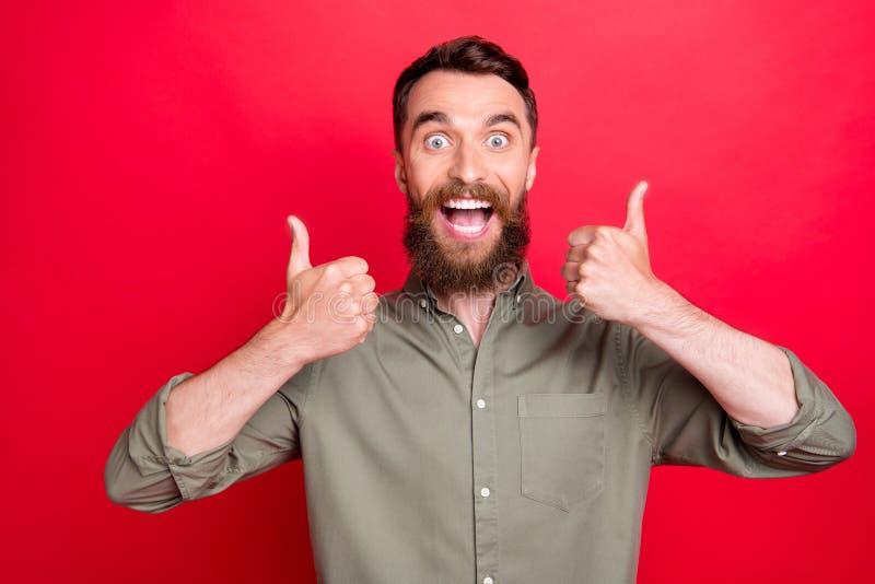 Foto dell'uomo estatico amichevole emozionante che è felice di comprare qualcosa mentre con fondo rosso immagini stock