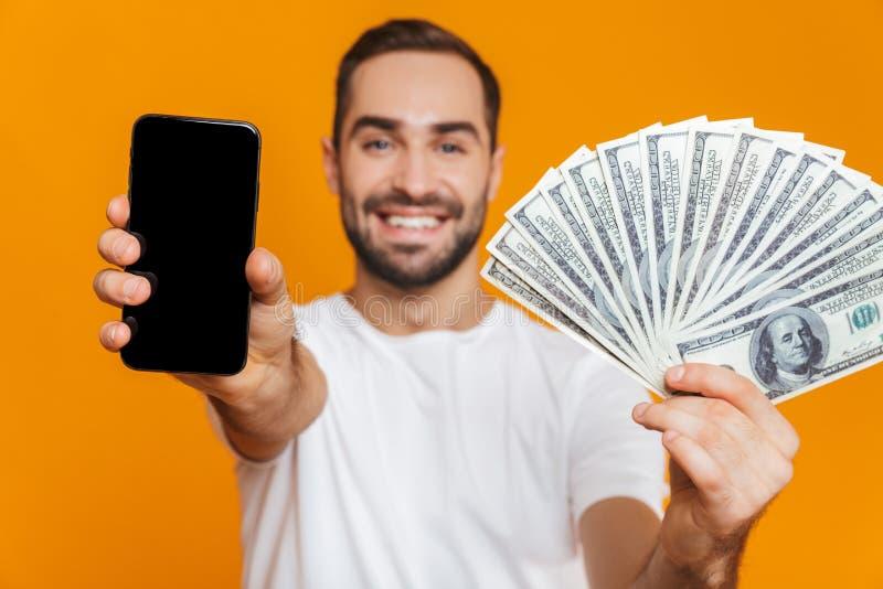 Foto dell'uomo europeo 30s nel telefono cellulare della tenuta di abbigliamento casual ed in fan di soldi, sopra fondo giallo fotografia stock libera da diritti