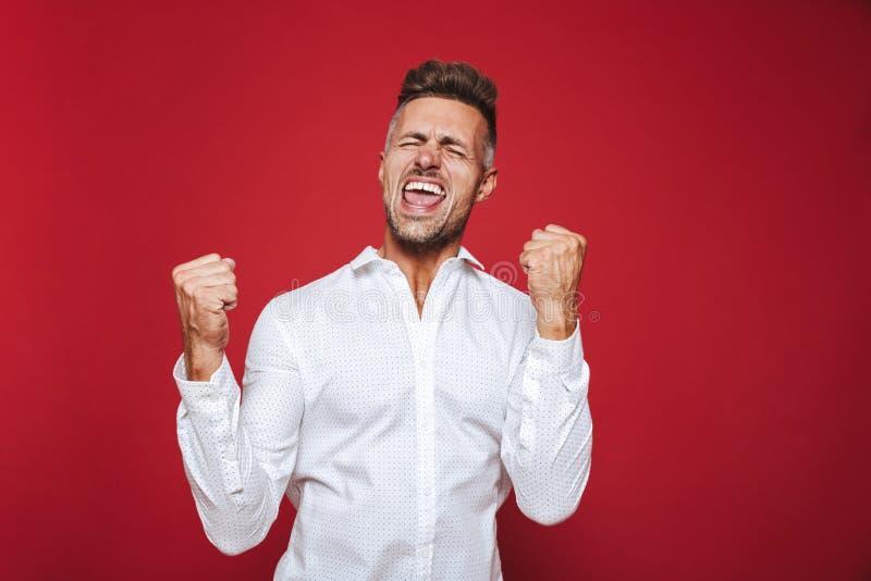 Foto dell'uomo ottimista nell'usura convenzionale che grida e che serra fi fotografia stock