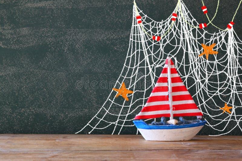 Foto della barca a vela di legno davanti alla lavagna con le illustrazioni nautiche immagine stock