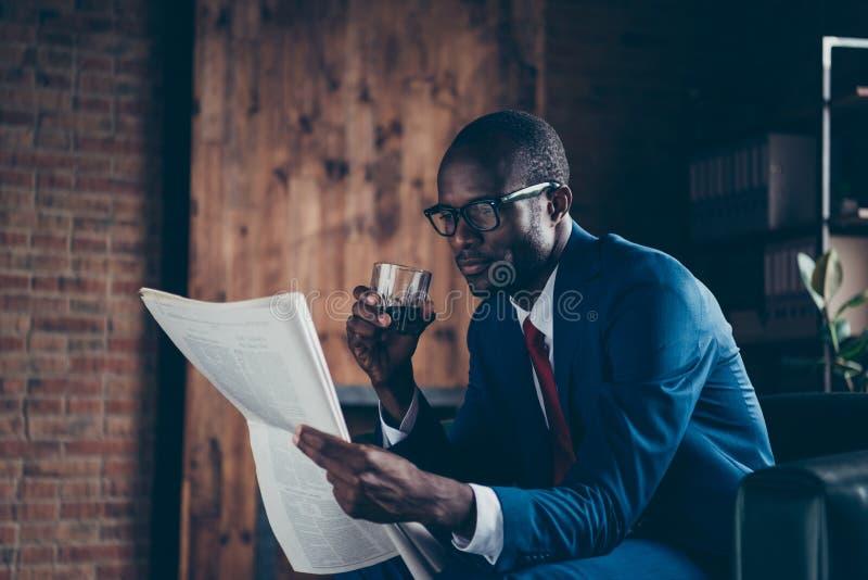 Foto della bevanda bevente di seduta dell'alcool del sofà dell'ufficio del tipo macho scuro della pelle che legge il costume eleg immagini stock libere da diritti