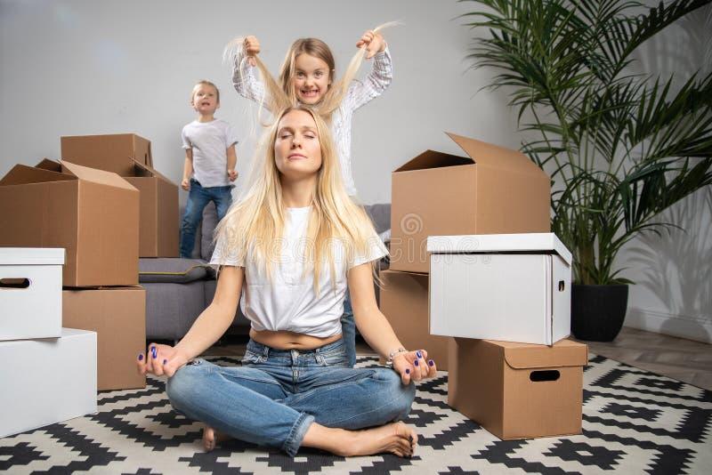 Foto della bionda calma che si siede sul pavimento fra le scatole di cartone ed il ragazzo, ragazza che salta sul sofà immagini stock