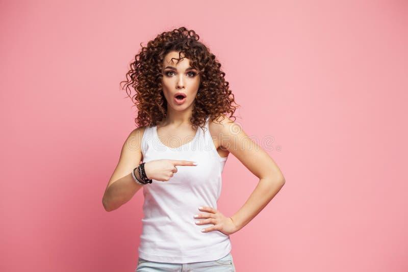 Foto della condizione felice della giovane donna isolata sopra il fondo rosa della parete Sguardo della macchina fotografica che  immagini stock libere da diritti