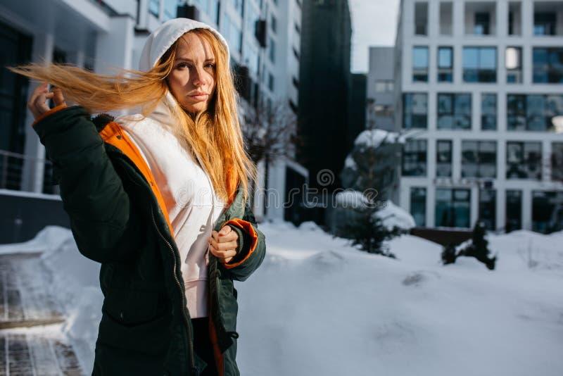 Foto della donna bionda in cappuccio e rivestimento contro il giorno di inverno fotografie stock libere da diritti