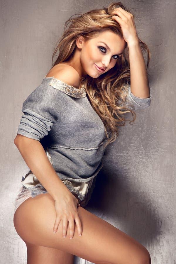 Foto della donna bionda sexy che mostra le gambe fotografia stock