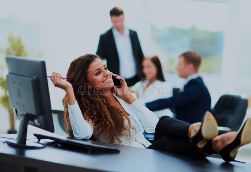 Foto della donna di affari sorridente che si siede con le gambe sullo scrittorio fotografia stock libera da diritti