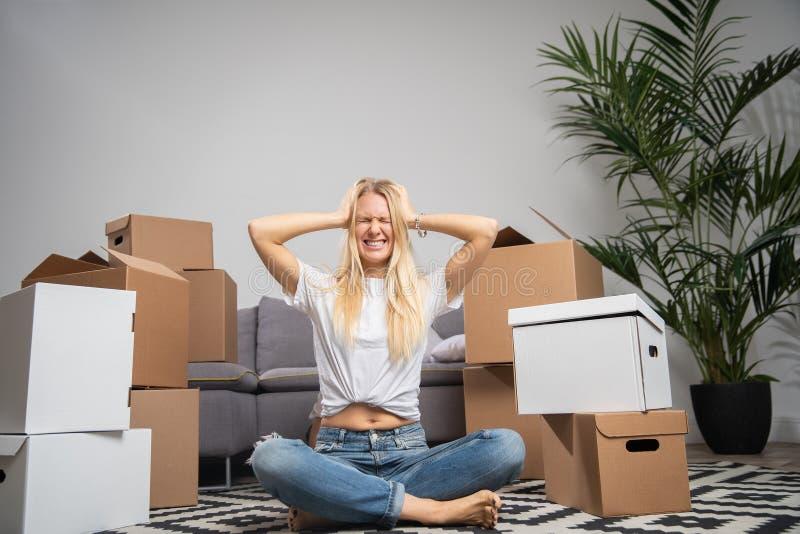 Foto della donna dispiaciuta che si siede sul pavimento fra le scatole di cartone immagini stock