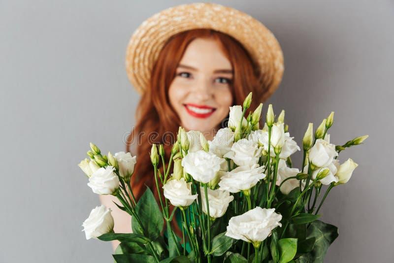 Foto della donna elegante 20s con il looki d'uso del cappello di paglia dei capelli rossi immagine stock libera da diritti