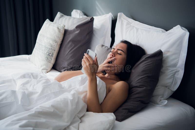 Foto della giovane donna graziosa all'interno a casa facendo uso della chiacchierata del telefono cellulare Lo sbadiglio si trova immagine stock libera da diritti