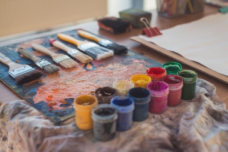 Foto della gouache e dell'acquerello con l'insieme di spazzole nello studio di arte Pitture ad olio spalmate sulla tavolozza fotografie stock libere da diritti