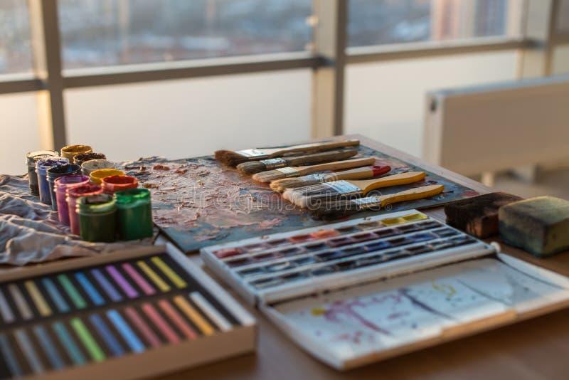Foto della gouache e dell'acquerello con l'insieme di spazzole nello studio di arte Pitture ad olio spalmate sulla tavolozza immagine stock