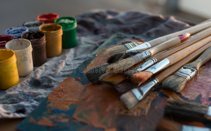 Foto della gouache e dell'acquerello con l'insieme di spazzole nello studio di arte Pitture ad olio spalmate sulla tavolozza immagini stock