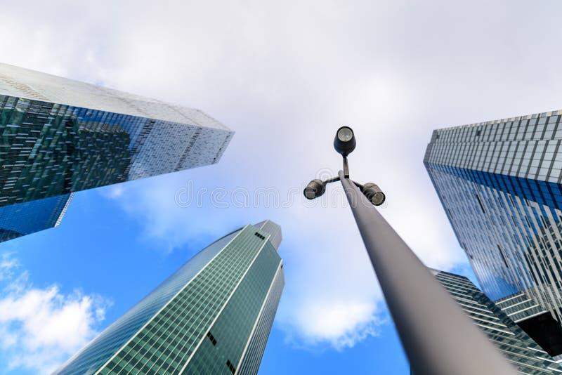 Foto della lampada di via o del lampione con i grattacieli vaghi nel fondo Centro di affari del concetto della città di Mosca immagini stock libere da diritti