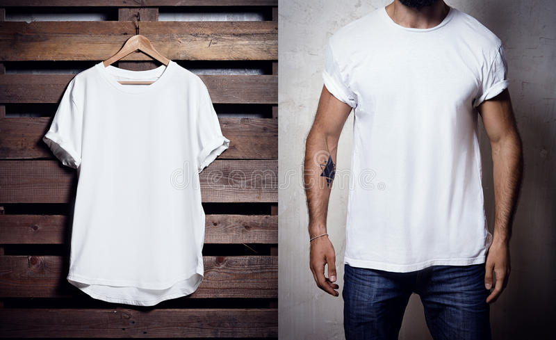 Foto della maglietta bianca che appende sul fondo di legno e sull'uomo barbuto che portano chiara maglietta Modello in bianco ver immagine stock libera da diritti