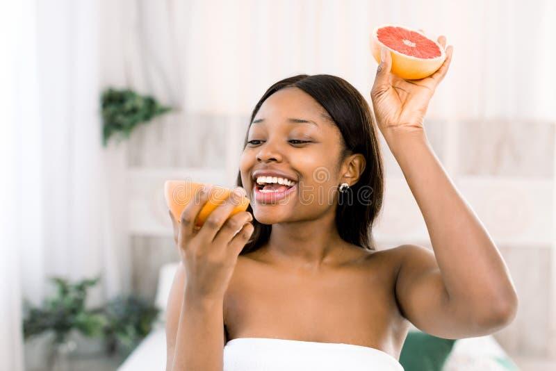 Foto della ragazza afroamericana che tiene una metà del pompelmo davanti al suo fronte e che sorride sul fondo leggero in stazion fotografie stock libere da diritti