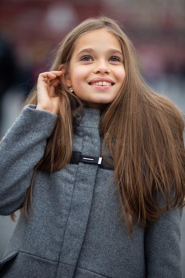 Foto della ragazza sorridente in cappotto grigio fotografie stock libere da diritti