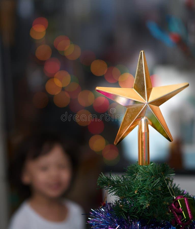 Foto della sfuocatura del sorriso del ragazzo mentre sguardo alla decorazione dorata della stella su chris immagini stock libere da diritti