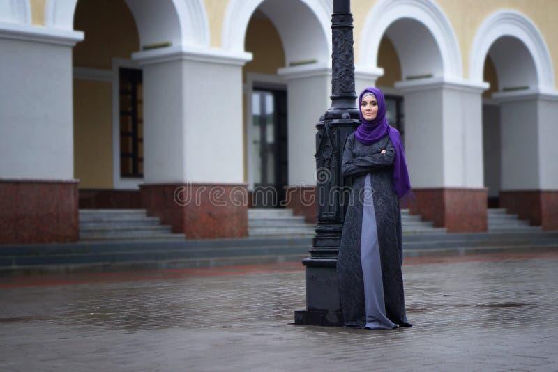 Foto della via una bella donna musulmana in vestito tradizionale sui precedenti della costruzione europea fotografia stock libera da diritti