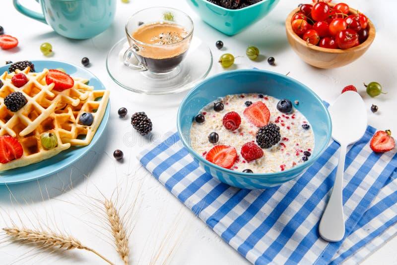 Foto delle cialde viennesi, farina d'avena, caffè, lamponi freschi, fragole, uva spina immagine stock