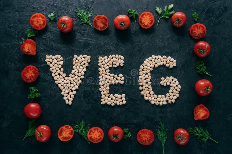 Foto delle lettere della struttura e del cece dei pomodori che significano veg Semi organici dentro del telaio di verdure isolato immagine stock