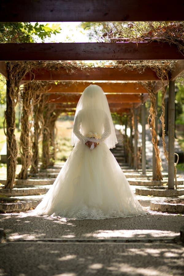 Foto delle mani della sposa che indicano indietro del fiore fotografia stock