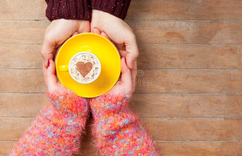 Foto delle mani maschii e femminili che tengono tazza di caffè sul wond fotografie stock