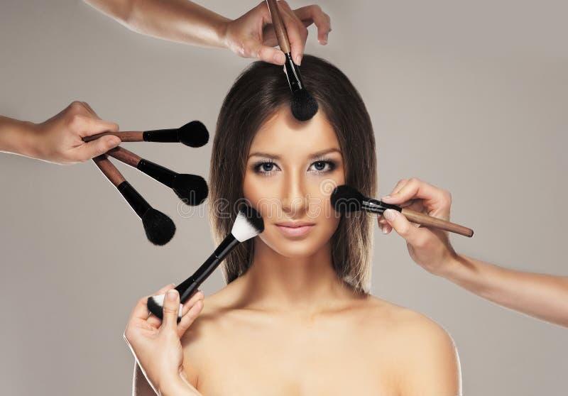 Foto dello studio del processo di trucco su una giovane donna fotografia stock
