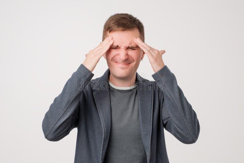 Foto dello studio di bella mostra caucasica dell'uomo quanto le sue ferite cape, avvertente dolore fotografie stock libere da diritti