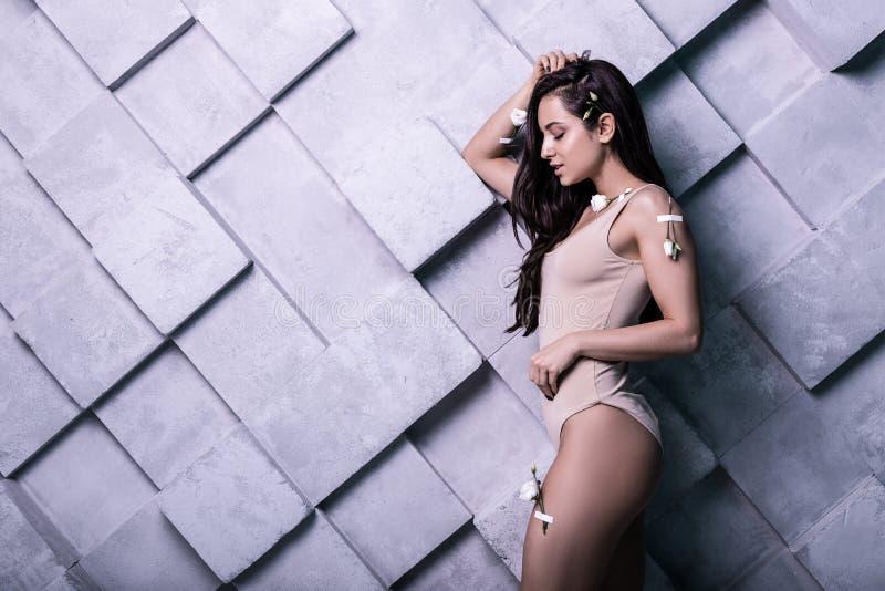 Foto dello studio di profilo di giovane modello attraente sopra fondo grigio immagine stock