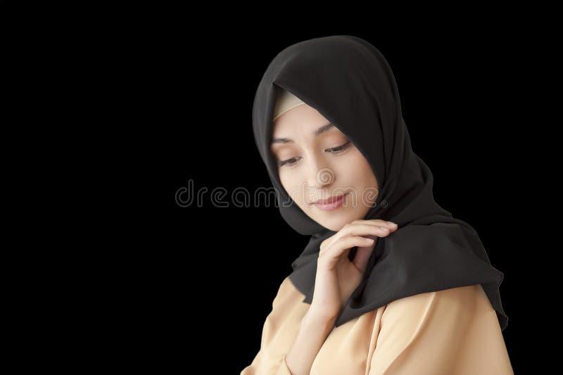 Foto dello studio di un tipo orientale della bella giovane donna integrale, su un fondo leggero, vestito nello stile musulmano immagini stock