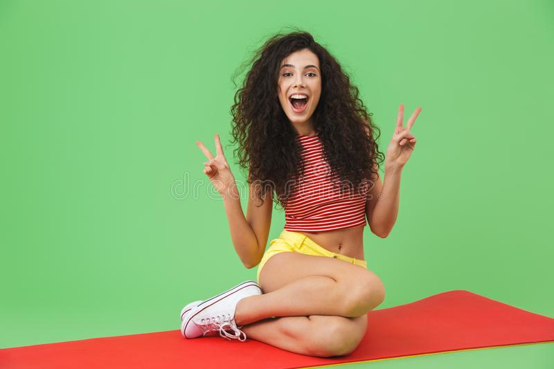 Foto der aktiven Eignungsfrau 20s, die auf Yogamatte während Aerobic lächelt und sitzt stockfoto