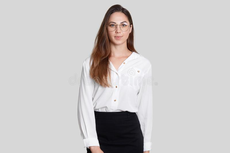 Foto der attraktiven eleganten Frau in der Geschäftsart, trägt transparente Gläser, weiße Bluse und schwarzen den Rock, lokalisie stockfoto