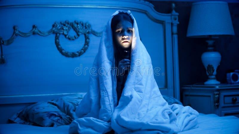 Foto der Bedeckung des kleinen Mädchens unter umfassender haltener Taschenlampe in der Dunkelkammer lizenzfreie stockbilder