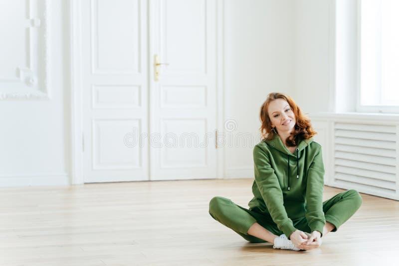 Foto der begeisterten Rothaarigefrau sitzt auf Lotoshaltung, trägt Trainingsnazug und ist in der guten Körperform, hat gelocktes  lizenzfreies stockbild