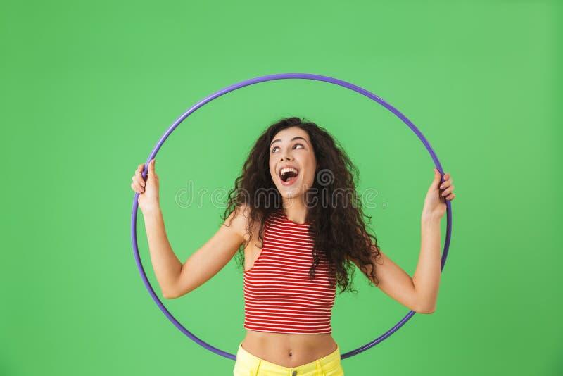 Foto der begeisterten tragenden Sommerkleidung der Frau 20s, die Übungen mit hula Band während der Gymnastik tut stockfoto