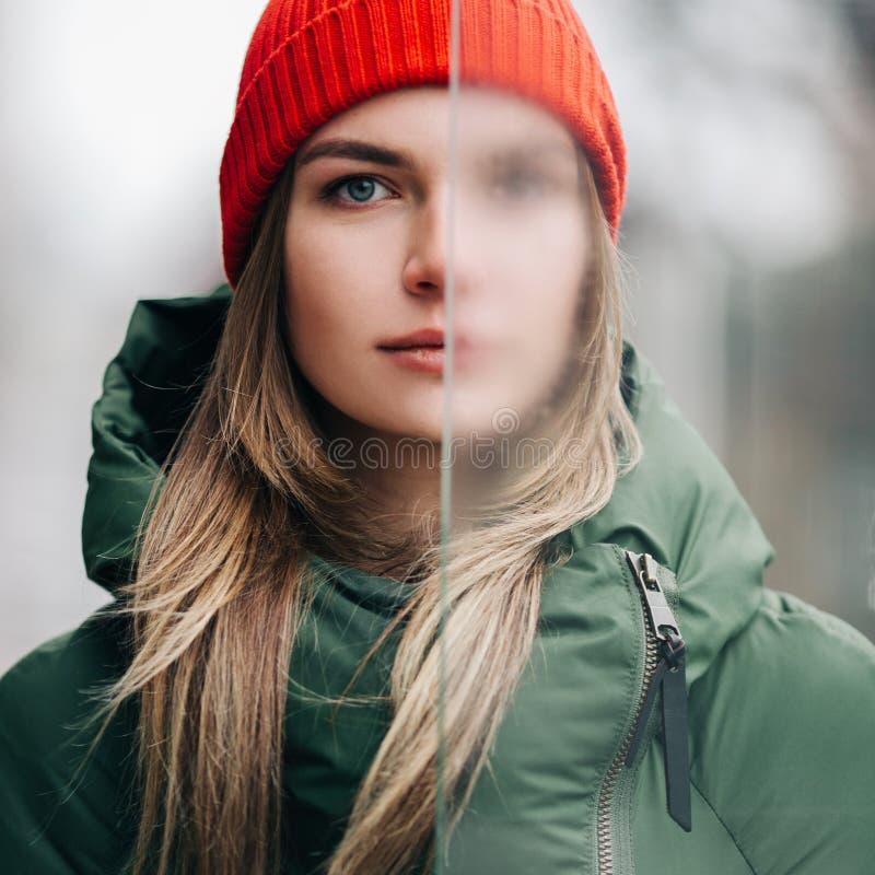 Foto der Blondine in der grünen Jacke und im roten Hut nahe Glas stockfoto