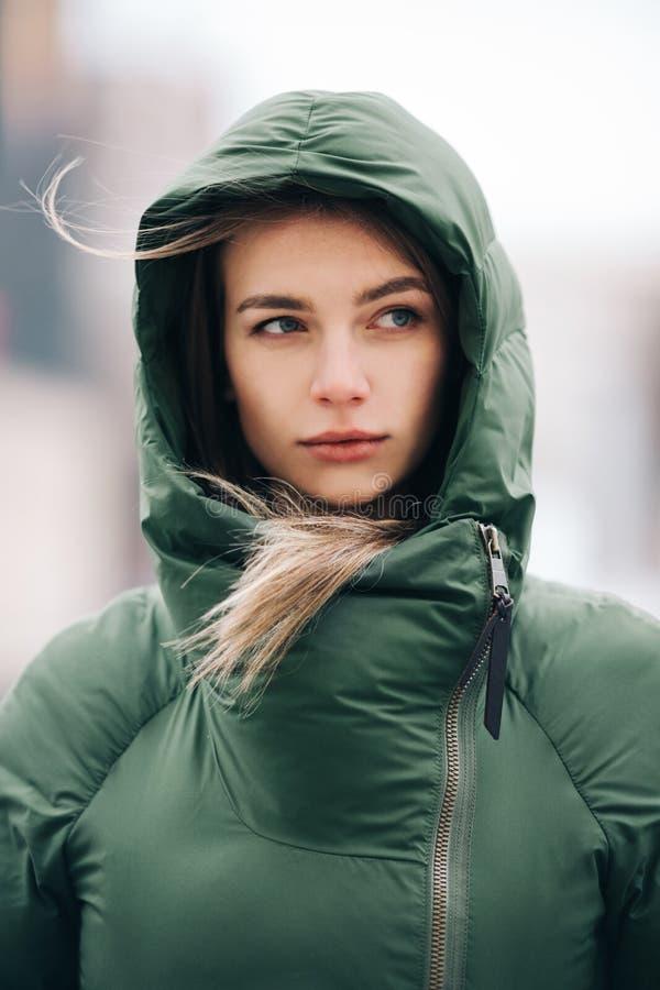 Foto der Blondine mit dem langen Haar in der grünen Jacke auf unscharfem Hintergrund stockfoto