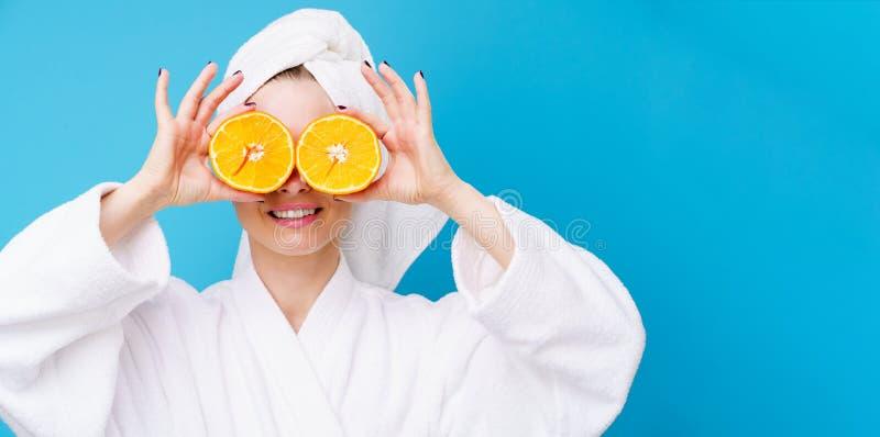 Foto der Frau im weißen Mantel mit Orangen nahe Augen lizenzfreies stockfoto