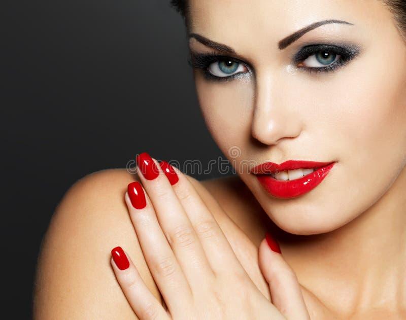 Foto der Frau mit den roten Nägeln und Lippen der Art und Weise lizenzfreies stockbild