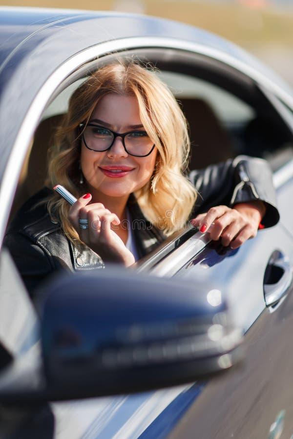 Foto der Frau mit Lippenstift in den Händen, die im Auto sitzen stockbild