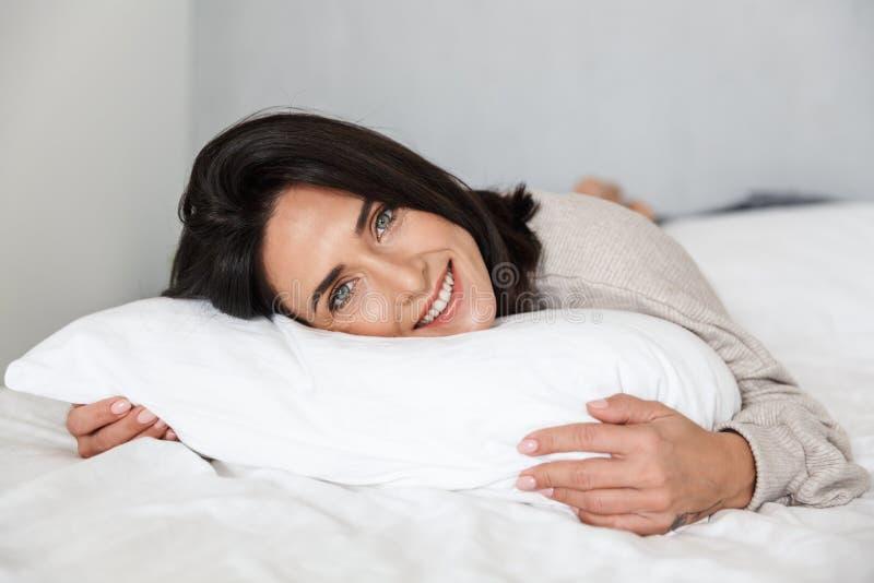 Foto der frohen lächelnden Frau 30s, beim im Bett mit weißem Leinen zu Hause liegen stockbilder