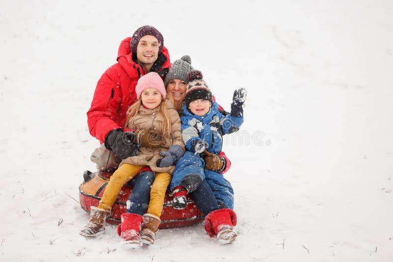 Foto der glücklichen Familie mit der Tochter und Sohn, die auf Schläuche im Winter sitzen stockfotografie