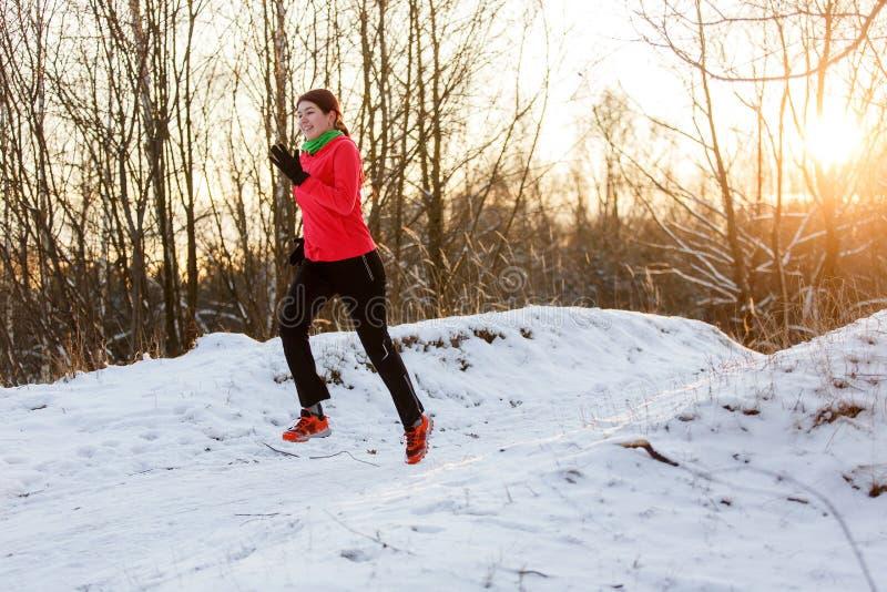 Foto der glücklichen Sportlerin auf Morgen laufen in Winter lizenzfreies stockbild