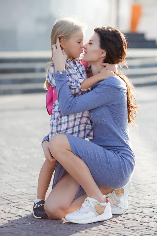 Foto der glücklichen Tochter und der Mutter, die draußen auf den Hintergrund der Stadt, das Wochenende zusammen verbringend geht stockbild