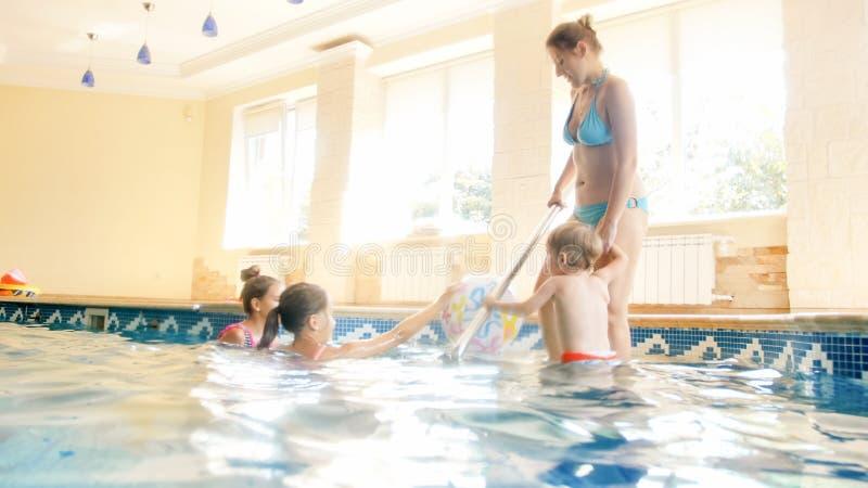 Foto der gl?cklichen netten Familie, die Spa? im Swimmingpool hat Junge Mutter mit drei Kindern in der Turnhalle mit Swimmingpool stockfoto