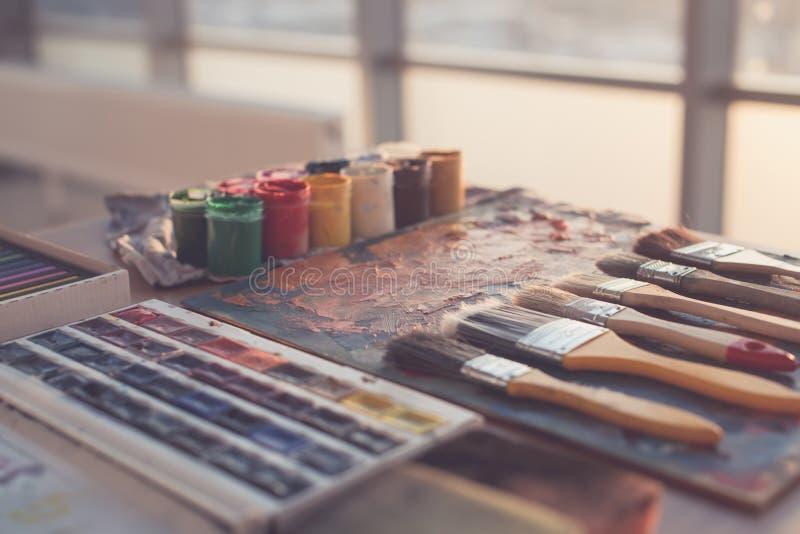 Foto der Gouache und des Aquarells mit Bürstensatz im Kunststudio Ölfarben geschmiert auf Palette lizenzfreie stockfotografie